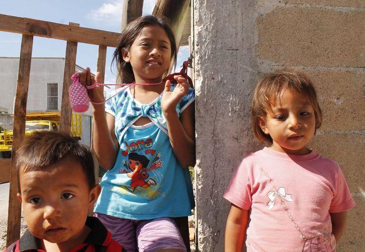 Michelle Pérez Pacheco (al centro) y sus hermanos esperan que Santa Claus no se olvide de visitarlos esta Navidad, en su casa ubicada en Rancho Viejo. (Jesús Tijerina/SIPSE)