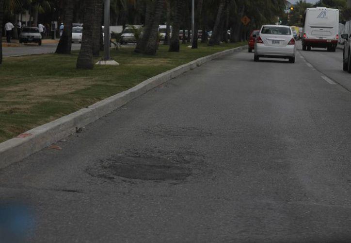 Algunos tramos del bulevar Kukulcán presentan baches. (Israel Leal/SIPSE)