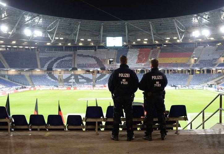 Policías vigilan las gradas del estadio de Hannover, donde se llevaría a cabo el partido Alemania-Holanda, cancelado por amenaza de bomba. (AP)