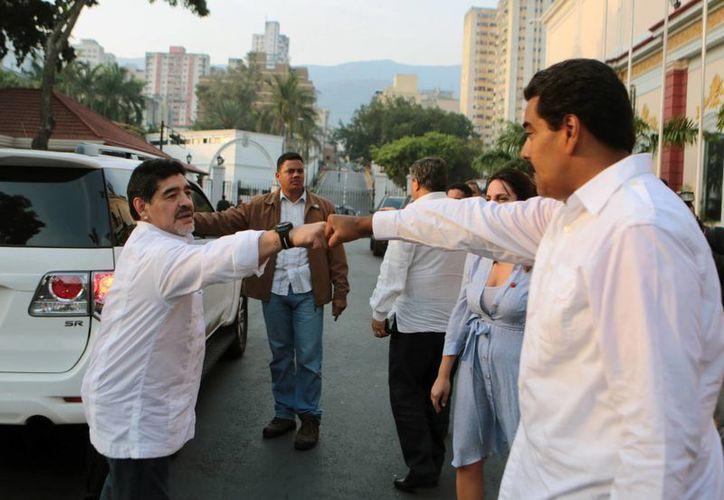 Diego Armando Maradona saluda a Nicolás Maduro al arribar ayer a la tumba del expresidente Hugo Chávez, donde lloró. (Agencias)