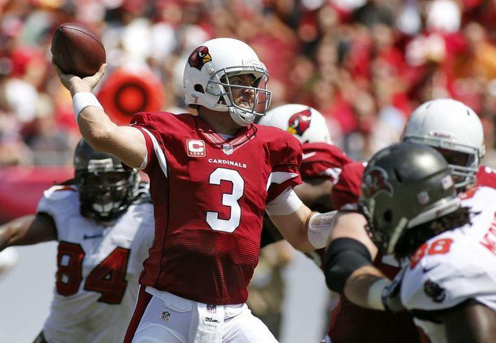 El quarterback de los Cardinals de Arizona Carson Palmer (3) lanza una pase en medio del asedio de la defensa de los Bucaneers de Tampa Bay. (Agencias)