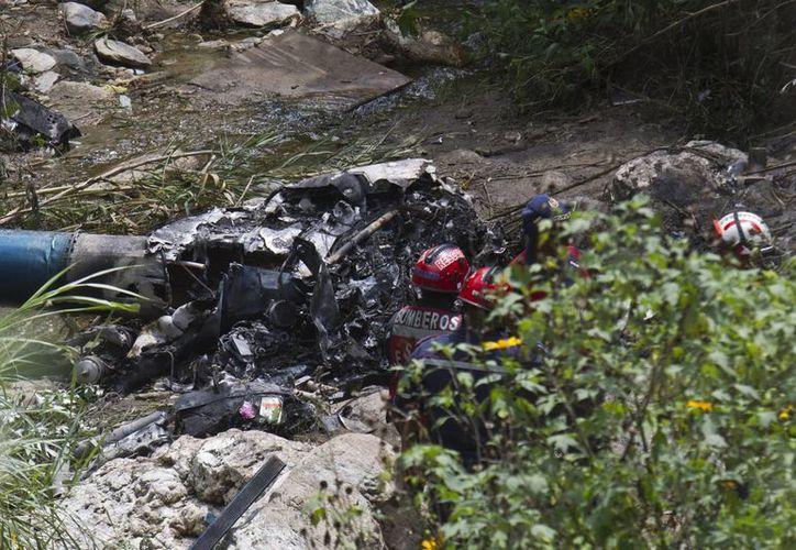 Bomberos asisten al lugar donde un helicóptero de la Policía Nacional Bolivariana se precipitó a tierra. (EFE)
