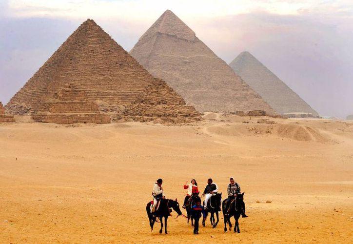 Turistas frente a las tres pirámides de Guiza. Casi todas las Maravillas del Mundo Antiguo han desaparecido o han sido destruidas al paso del tiempo. (Foto de Flick vision)