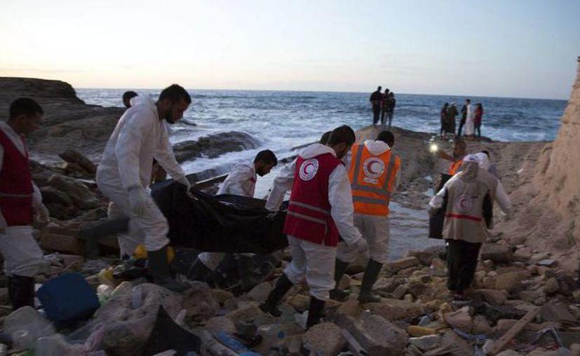 Miembros de la Media Luna Roja Libia (LRC) cargan un cuerpo en las costas de al-Maya, el 10 de noviembre de 2016. (EFE)
