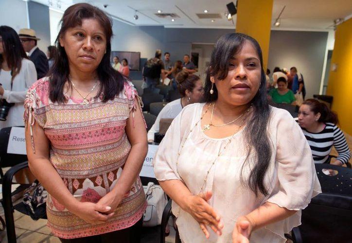 Florentina Donato Sánchez (izq) y María Montserrat Martínez Mejía, hablan del programa para que 200 poblanos viajen a Estados Unidos a ver a sus familias, en el consulado de México en Nueva York, el lunes 20 de junio de 2016. (AP Foto/Richard Drew)