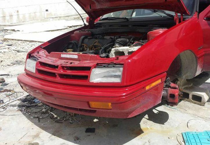 La unidad Chrysler, tipo Shadow, rojo, se encontraba desvalijada. (Eric Galindo/SIPSE)