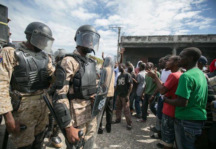 Partidarios de la candidata a la presidencia de Haití por el partido Fanmi Lavalas se enfrentan con miembros de la policía durante una manifestación en las calles de Puerto Príncipe. (EFE)
