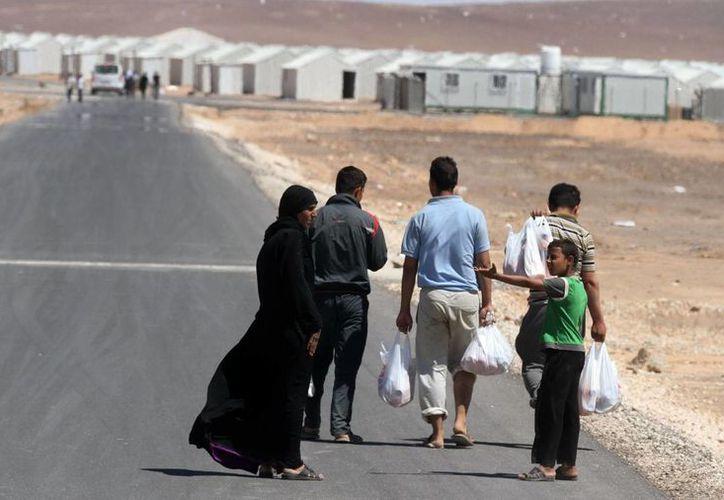 Una familia se encamina hacia el nuevo campamento de refugiados sirios de Azraq, que se extiende por 15 km en Jordania, junto a la frontera con Siria, el miércoles 30 de abril del 2014. (Foto: Raad Adayleh/AP)