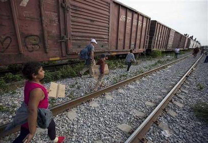 En foto del 12 de julio de 2014 se ve a migrantes caminar por las vías del tren en Ixtepec, Oaxaca, México, durante su recorrido hacia la frontera entre este país y Estados Unidos. (Foto de AP/Eduardo Verdugo)