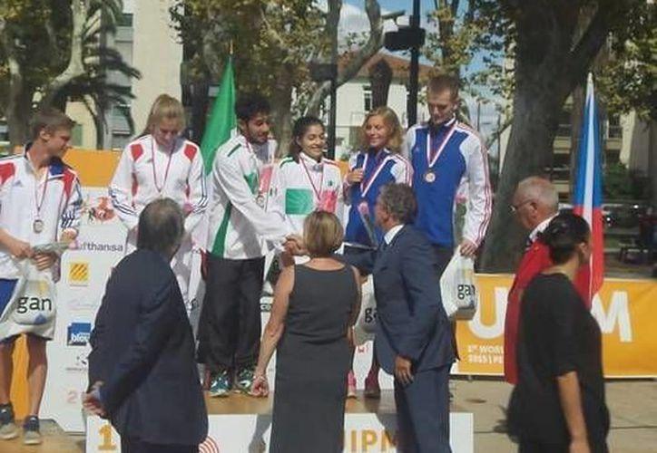 Durante el campeonato mundial de tiro carrera, la jalisciense Xóchitl Olivares y el neolonés Andrés Garza (centro) consiguieron el sitio de honor dentro del pódium en relevos mixtos, en el torneo realizado en Francia.(Twitter: @CONADE)