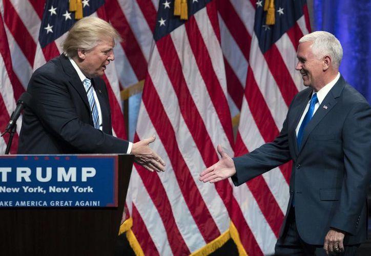 El candidato presidencial republicano Donald Trump estrecha la mano de Mike Pence durante un acto de campaña para anunciarlo como el candidato a  vicepresidente. (Agencias)