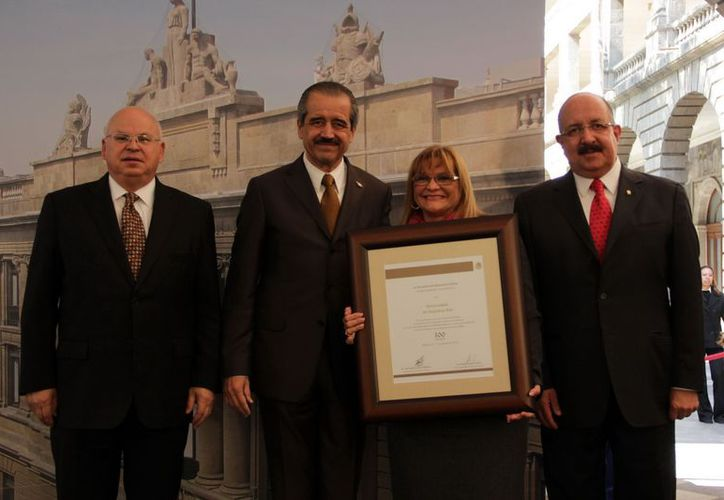 La rectora de la Universidad de Quintana Roo, Elina Coral Castilla, recibió de manos del secretario de Educación, José Ángel Córdoba Villalobos. (Cortesía/SIPSE)