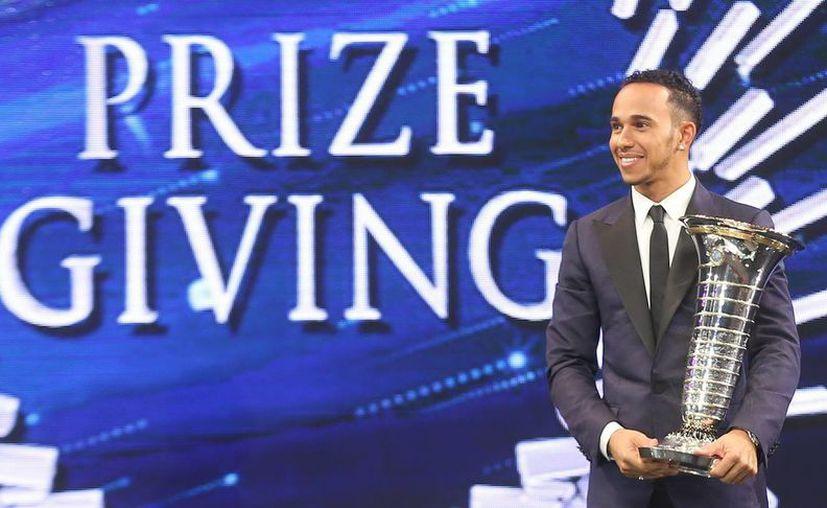 El piloto inglés Lewis Hamilton con el reconocimiento de la BBC como mejor deportista del año, galardón que compartió con el futbolista Cristiano Ronaldo, aunque este como extranjero. (EFE)