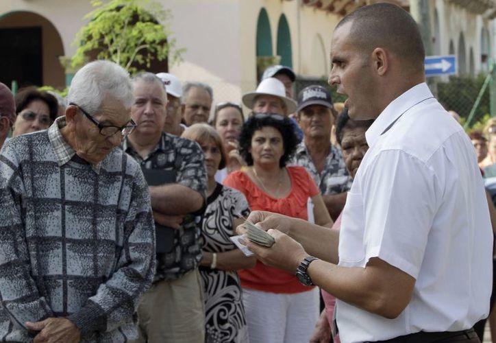 Varias personas esperan ingresar a la Sección de Intereses de Estados Unidos en La Habana para solicitar la visa. (Agencias)