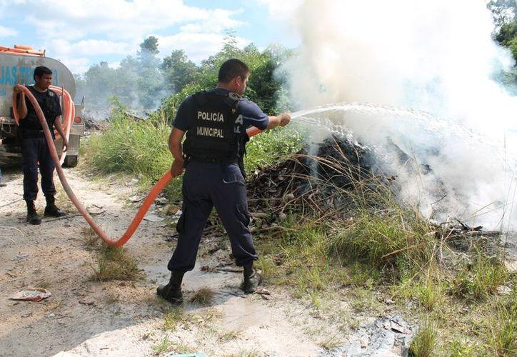 Los elementos municipales fueron quienes se hicieron cargo del fuego en un vertedero de basura pasando el nuevo cementerio. (Juan Carlos Gómez/SIPSE)