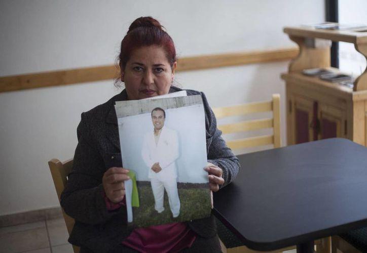 La señora Griselda Barradas sostiene una foto de su hijo Pedro Huesca Barradas, quien fue levantado hace casi cuatro años. (Saúl Ruiz/El País)