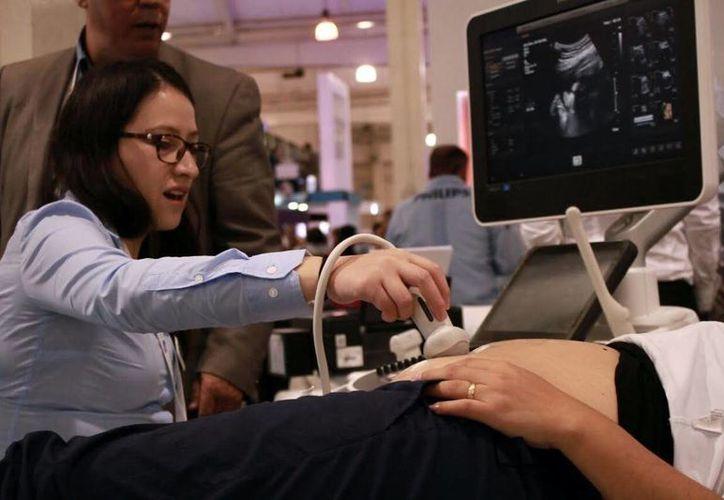Arturo Perea Martínez, presidente de la Academia Mexicana de Pediatría, negó que los estudios de ultrasonido que se realizan a las mujeres embarazadas causan algún daño al bebé. Imagen de contexto de una especialista realizando este examen a una mujer. (Milenio Novedades)