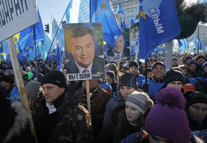 Simpatizantes del gobernante ucraniano Viktor Yanukovych muestran retratos del presidente en un mitin de apoyo, para contrarrestar las protestas en contra del mandatario. (Agencias)