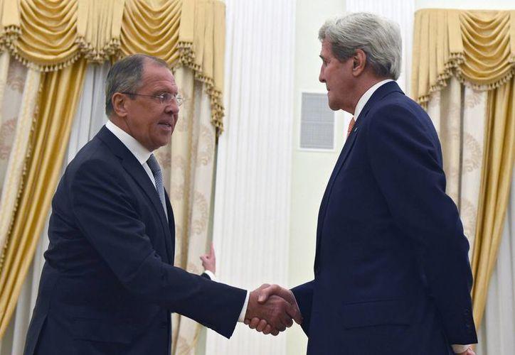 El secretario de Estado de EU, John Kerry (d), estrecha la mano de su homólogo ruso, Sergei Lavrov (i) tras llegar a un acuerdo sobre los movimientos que ambos países realizan en Siria. (EFE)