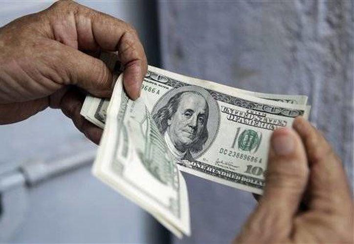 El dólar se adquirió en un mínimo de 14.29 pesos en bancos del Distrito Federal. (Archivo/AP)