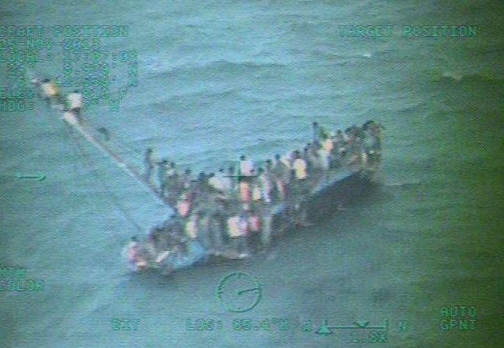 Fotos de escasa definición mostraron a un centenar de personas aferrándose como podían al casco de la nave volcada. (Agencias)