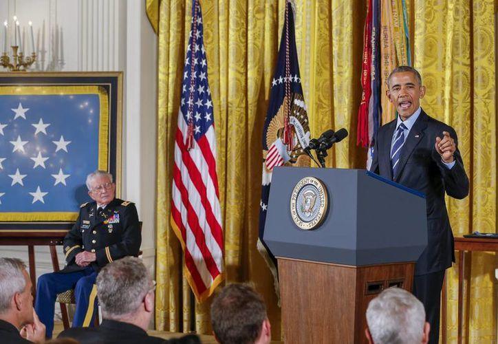 El presidente Barack Obama (d) ofrece un discurso durante la ceremonia de la Medalla de Honor al retirado teniente coronel Charles Kettles (i) en la Sala Este de la Casa Blanca en Washington. (EFE)