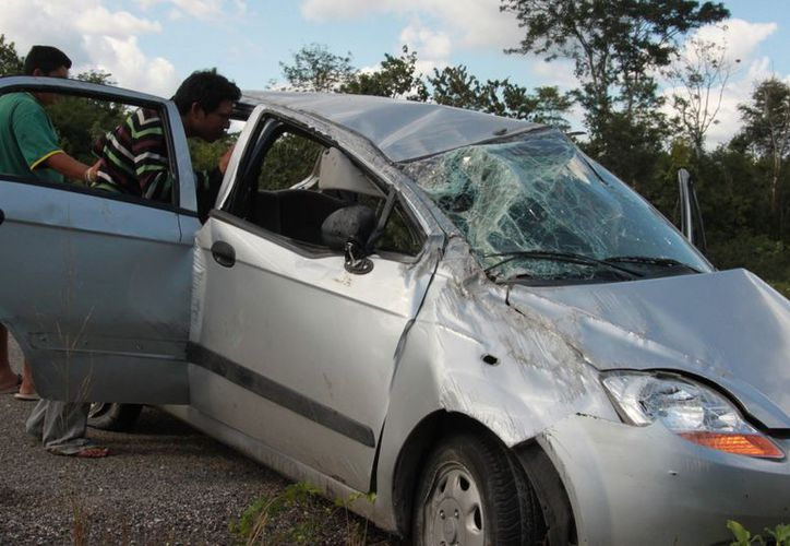 Conductores que transitaban por la  carretera llamaron al número de emergencias 066 para reportar los hechos y solicitar la presencia de los cuerpos de emergencia, ya que una persona estaba atorada dentro de la unidad. (Manuel Salazar/SIPSE)