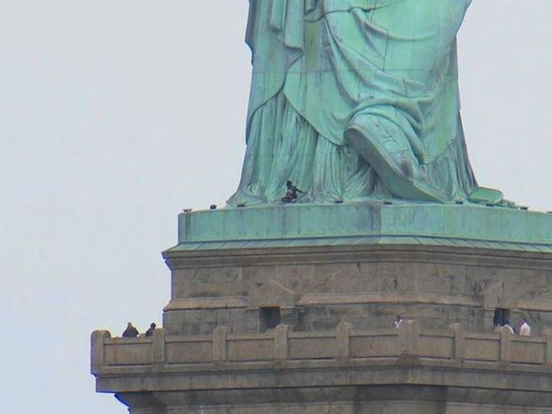 IN this image made from video by PIX11, a person, center, leans against the robes of the Statue of Liberty on Liberty Island.