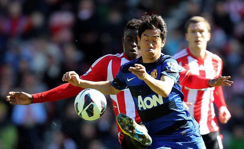 El japonés Shinji Kagawa (azul), del Manchester United, protege el balón. (Agencias)