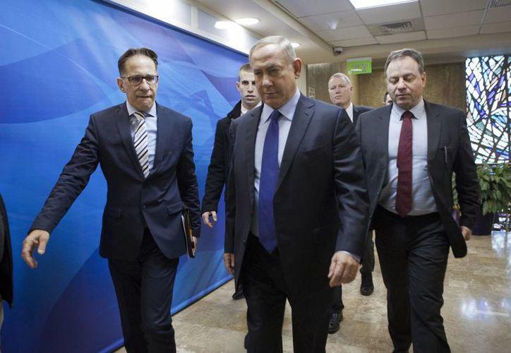 El primer ministro israelí Benjamin Netanyahu (c) insiste que no hay nada malo en su controversial política de construir poblados judíos en áreas ocupadas que los palestinos reclaman. En la foto, en su arribo para un mitin en Jerusalén, este domingo.
