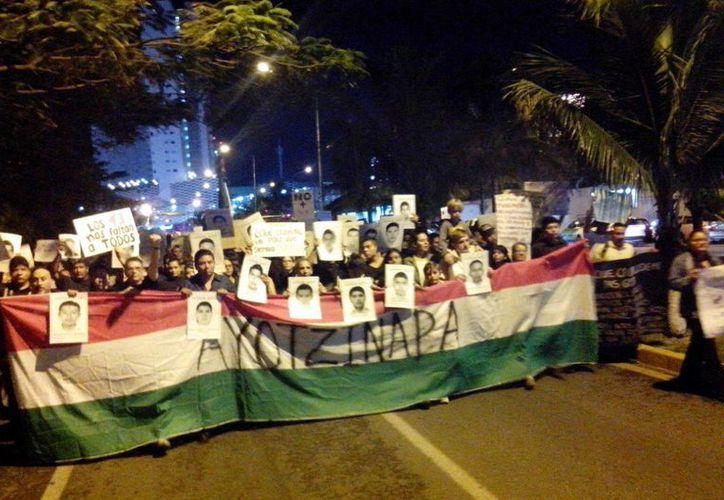 Más de mil personas marchan en protesta por la desaparición de los 43 normalistas de Iguala. (Sergio Orozco/SIPSE)