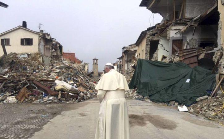 Francisco reza delante de los escombros que dejó el terremoto en la ciudad de Amatrice, Italia. (Greg Burke/Oficina de Prensa del Vaticano a través de AP)