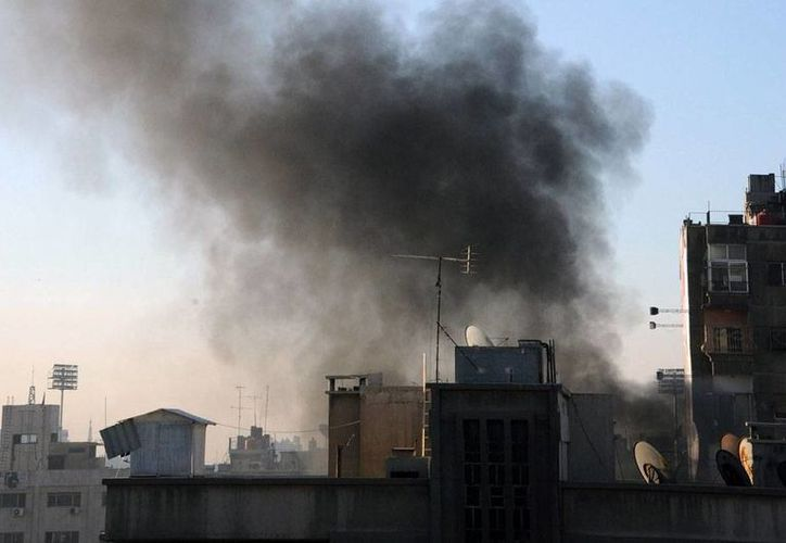Imagen tomada por la agencia SANA en la que pueden verse columnas de humo de los bombardeos del régimen sirio en Damasco. (AP)