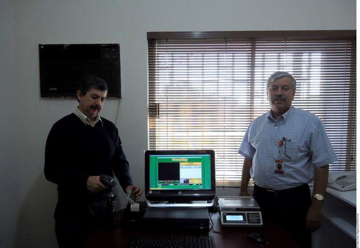 Enrique Flores (izq.) y Homero Villarreal muestran el punto de venta que consiste en una computadora, impresora y escaner, que funciona con un software de su desarrollo. (Agencia Reforma)