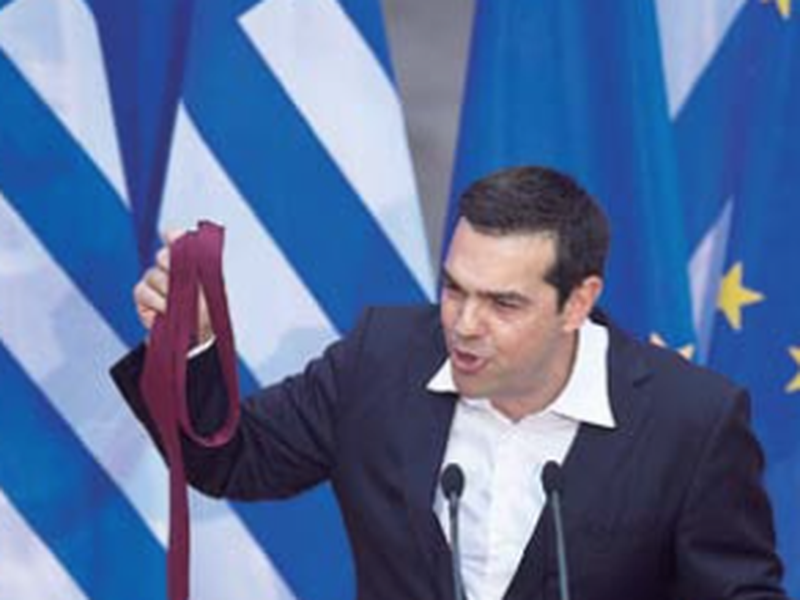 Greek Prime Minister Alexis Tsipras hold a tie he just removed his at the end of a speech to lawmakers. (AP)