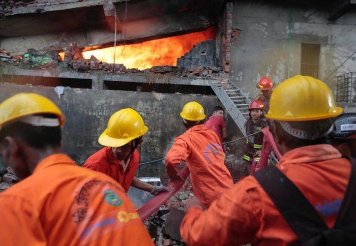 Bomberos trabajan para controlar las llamas en una fábrica de embalajes en la zona industrial de Tongi, en las afueras de Dacca, Bangladesh. (AP/A. M. Ahad)