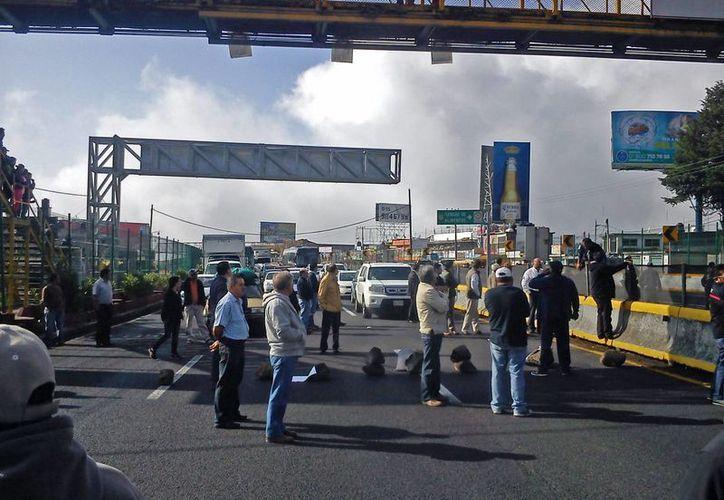 Los inconformes mantienen bloqueados ambos sentidos de la autopista México-Cuernavaca. (Notimex)