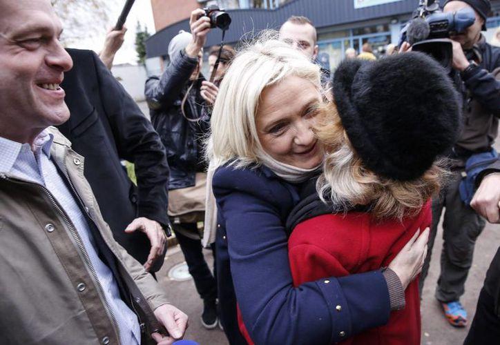 La líder del partido de Frente Nacional (FN) Marine Le Pen (c) abraza a sus seguidores tras emitir su voto en la primera vuelta de las elecciones regionales francesas en Henin-Beaumont, Norte de Francia. (EFE)