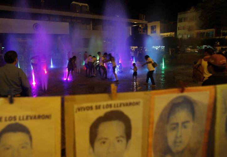 Un grupo de niños juega en una fuente recientemente inaugurada fuera de la oficina de gobierno de Iguala, México. La fuente tiene luces de colores y está rodeada por afiches alusivos a los 43 estudiantes desaparecidos. (Agencias)