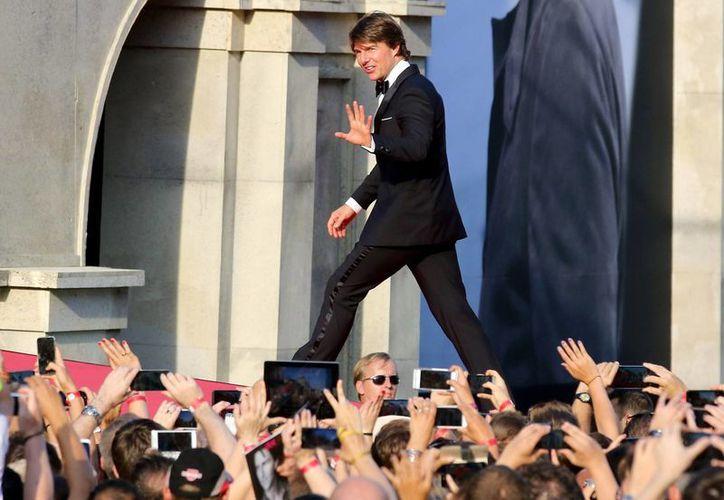 Tom Cruise saluda a sus admiradores en el estreno mundial de 'Mission Impossible–Rogue Nation' en la Ópera de Viena en Austria, que se llevó a cabo hoy jueves 23 de julio. (AP)