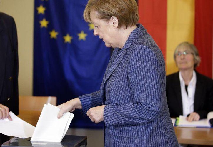 La canciller Angela Merkel emite su voto para elegir al nuevo Parlamento Europeo, con sede en la capital de Bélgica. (AP)