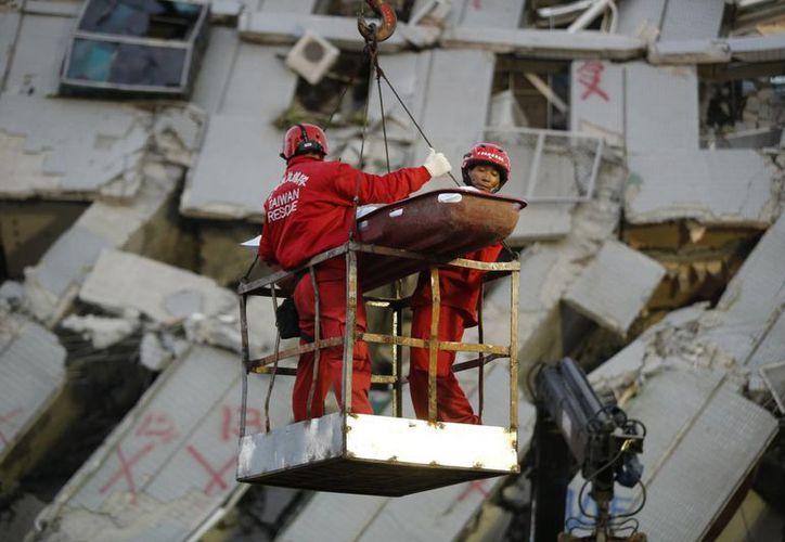 Dos socorristas transportan a una víctima retirada de entre los restos de un edificio de apartamentos en Tainan, Taiwán, zona que fue azotada el sábado pasado por un sismo de 6.4. (Agencias)