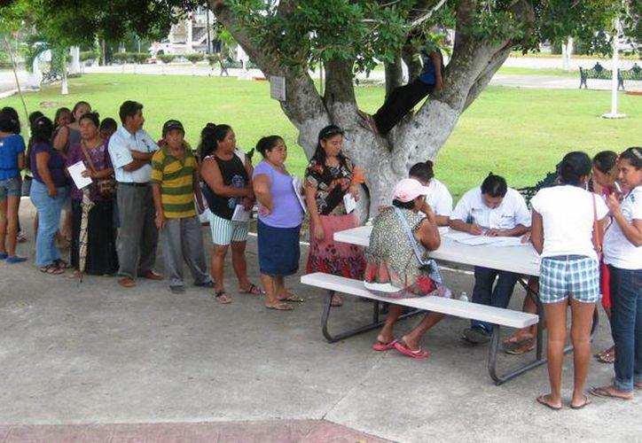 En el parque principal de la ciudad, se formaron largas filas de amas de casa que acudieron a renovar su tarjeta de Prospera. (Javier Ortiz/SIPSE)