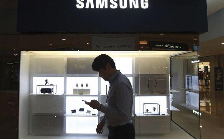 Un hombre pasa frente a una tienda de Samsung en Seúl, Corea del Sur. Samsung deberá pagar una suma millonaria a Apple por copiar algunos de sus diseños. (AP Photo/Ahn Young-joon)