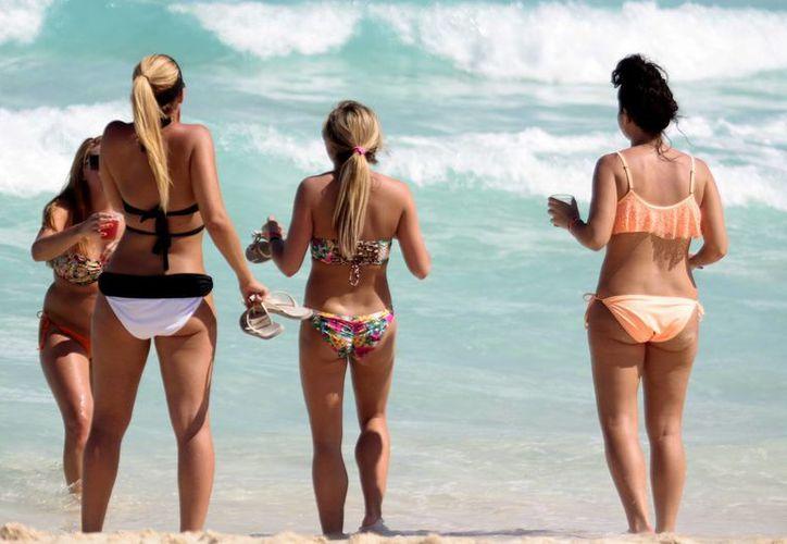 Un grupo de turistas disfruta en bikini las playas de Cancún, Quintana Roo. Imágenes como ésta quieren evitar en el estado de Goa, India. (Foto de contexto. Notimex)