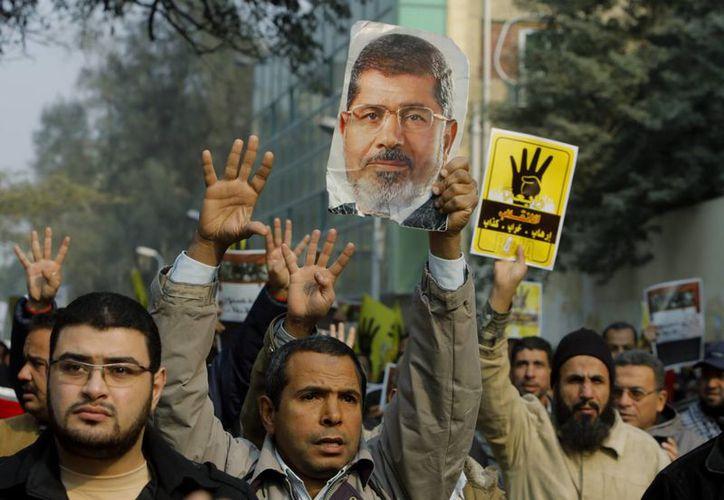 Simpatizantes del derrocado presidente de Egipto Mohammed Morsi portan banderas con un logo que representa una mano con cuatro dedos extendidos que se ha convertido en un símbolo de la mezquita Raba al-Adawiya. (Agencias)