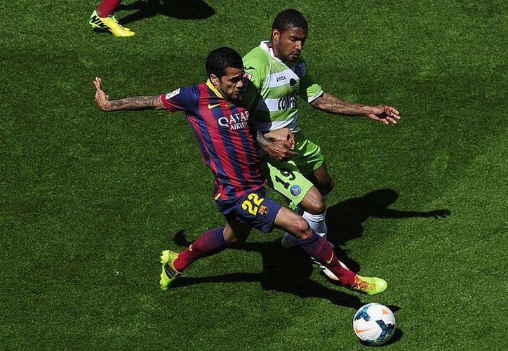 Danni Alves intenta hacer una jugada ofensiva ante el Getafe. Al final el Barza echó por tierra la liga local. (Foto: AP)