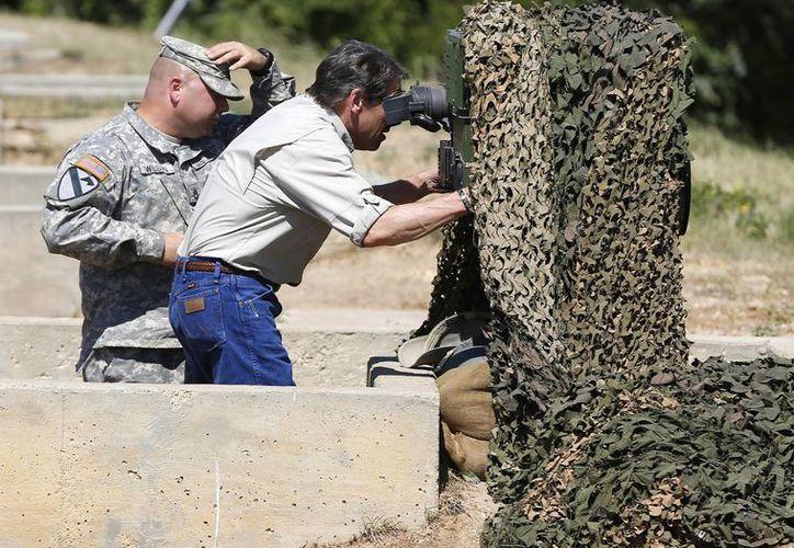 El gobernador de Texas, Rick Perry, examina un aparato de visión en Camp Swift, en Bastrop, Texas, donde se entrena la Guardia Nacional, este 13 de agosto de 2014. (Foto: AP)