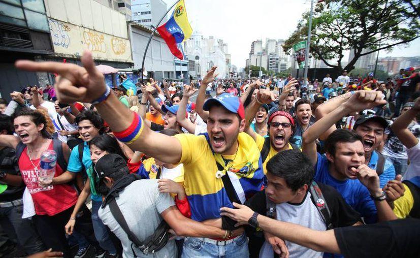 Estudiantes de la oposición cantan consignas contra los simpatizantes del fallecido presidente Hugo Chávez durante una protesta. (Agencias)
