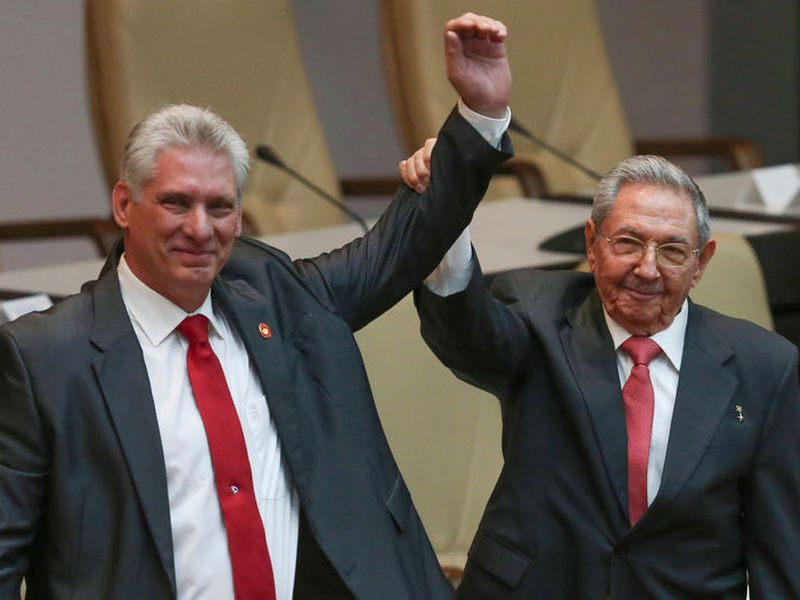 Cuba's outgoing President Raul Castro, right, and new President Miguel Diaz-Canel raise their arms in unison at the National Assembly in Havana, Cuba. Castro said Thursday that he expected the 57-year-old Diaz-Canel to serve two five-year terms as president and eventually take Castro's place. (AP)